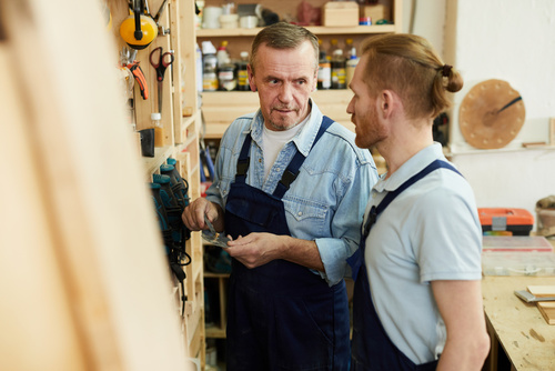 Portrait of senior carpenter talking to young trainee while work