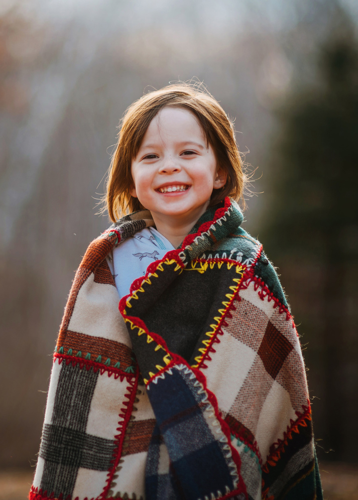 Portrait of a girl wrapped in a patchwork quilt